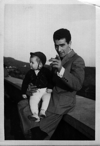 my father holds my brother in 1964, pointing to my mother taking the picture unseen | by Paolo Ippoliti