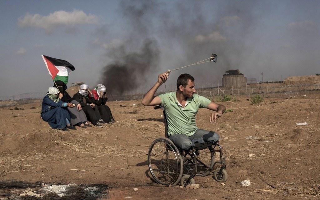 在加薩邊境,一名無腿的巴勒斯坦人用吊索對以色列部隊投擲石塊。(攝影:Etienne De Malglaive/Getty)