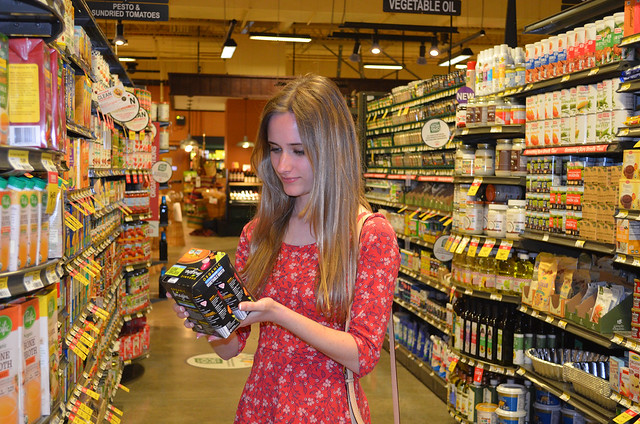 A young lady holds a package in a supermarket