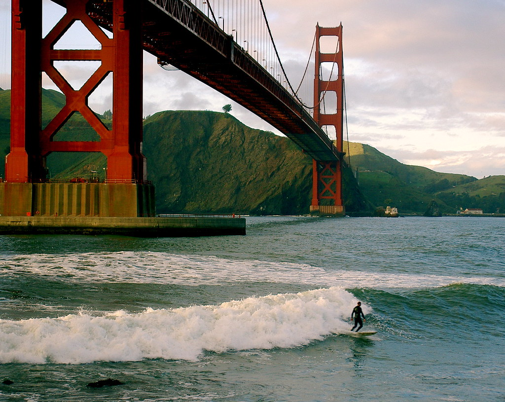 sunset surfer under golden gate bridge