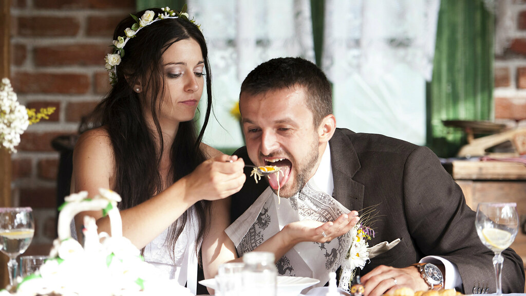 Groom being fed by bride