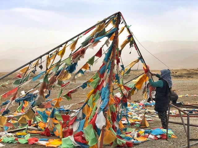 Colocando banderolas de colores a orillas del lago Qinghai (China)