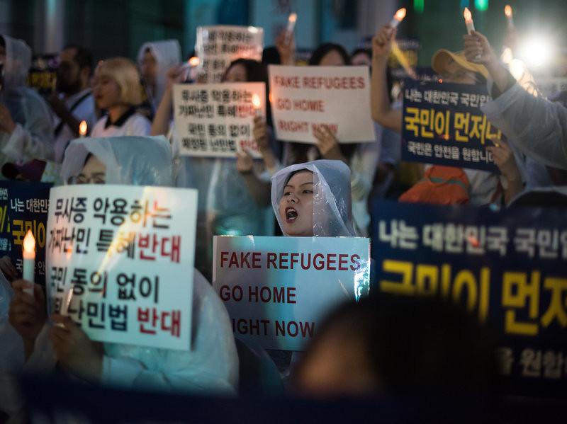 """6月30日,首尔一场拒绝叶门难民的抗议场合中,一名女子举着""""假移民立刻回家""""的标语。(图片来源:Ed Jones/AFP/Getty Images)"""