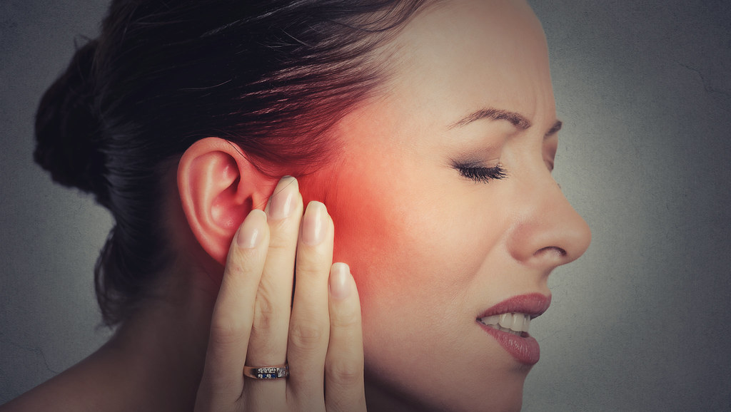Woman holding ear - in pain.