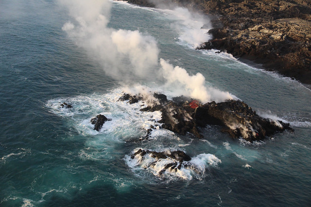 Image shows a black coastline of fresh lava, and a steaming tiny pile of lava emerging from the blue water a short distance away from the new coastline. The center of the mound is glowing red; the rest is black. Waves are breaking against the rocky black reefs fringing the new island