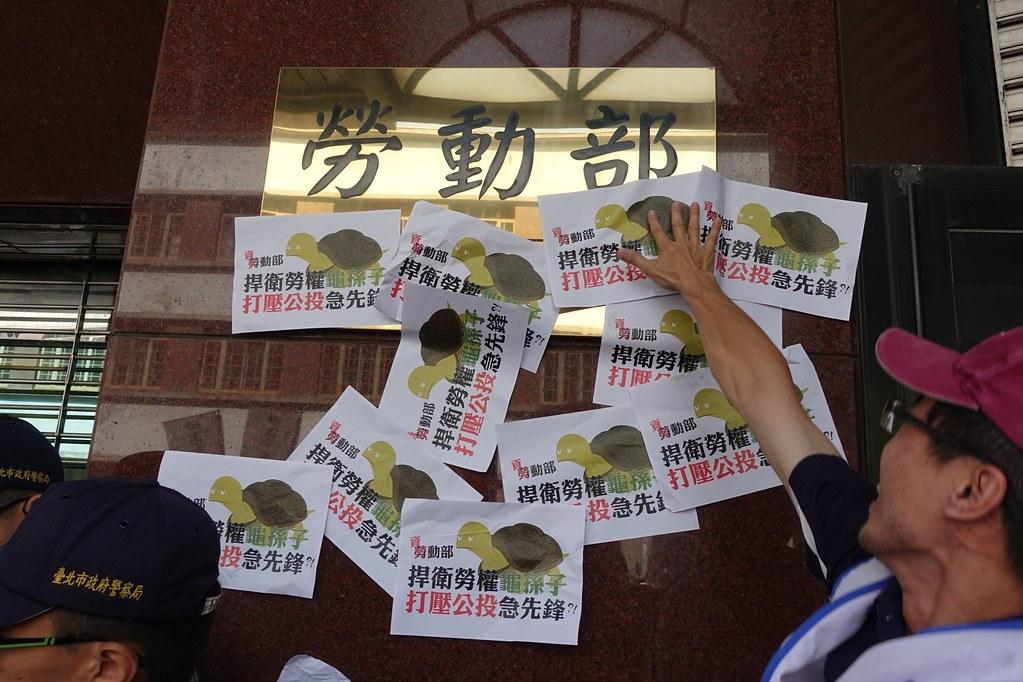 """劳动部被贴上""""劳权龟孙子""""的抗议标语。(摄影:张智琦)"""