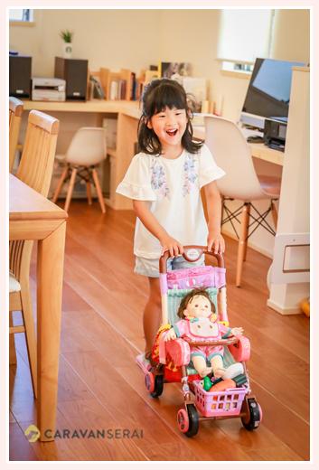 おもちゃのカートに人形を乗せて動かす女の子