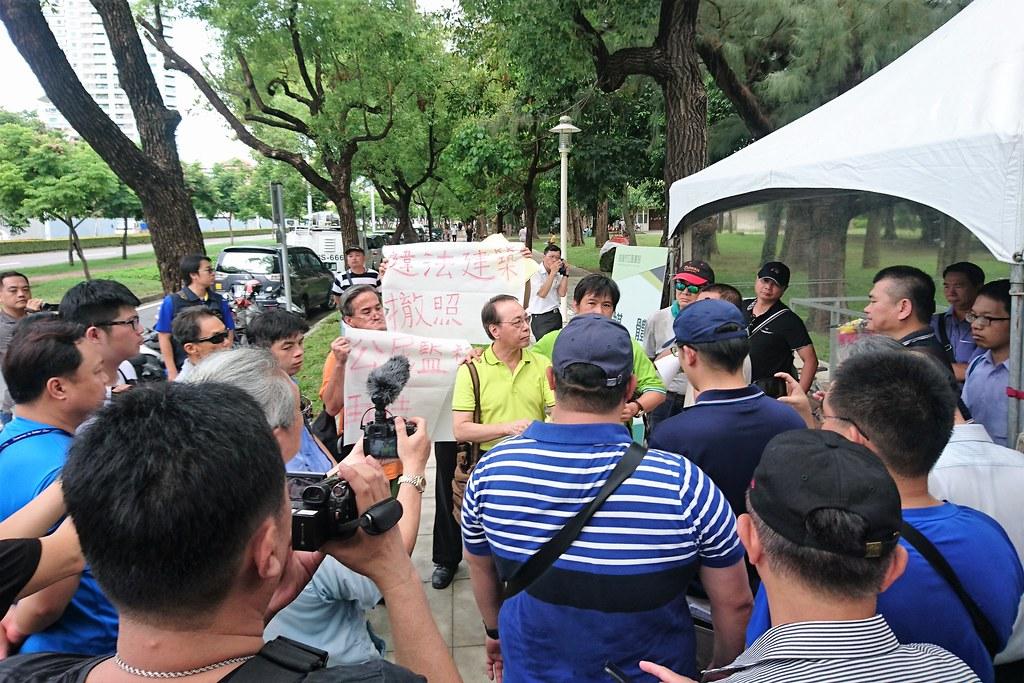 高雄市護樹護地協會在場外抗議遭警力層層包圍。攝影:李育琴