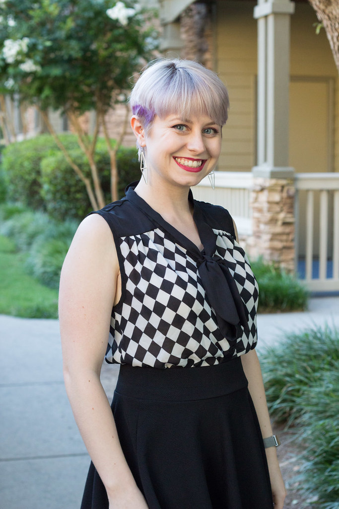 Blonde pixie cut with a checkered bow front shirt