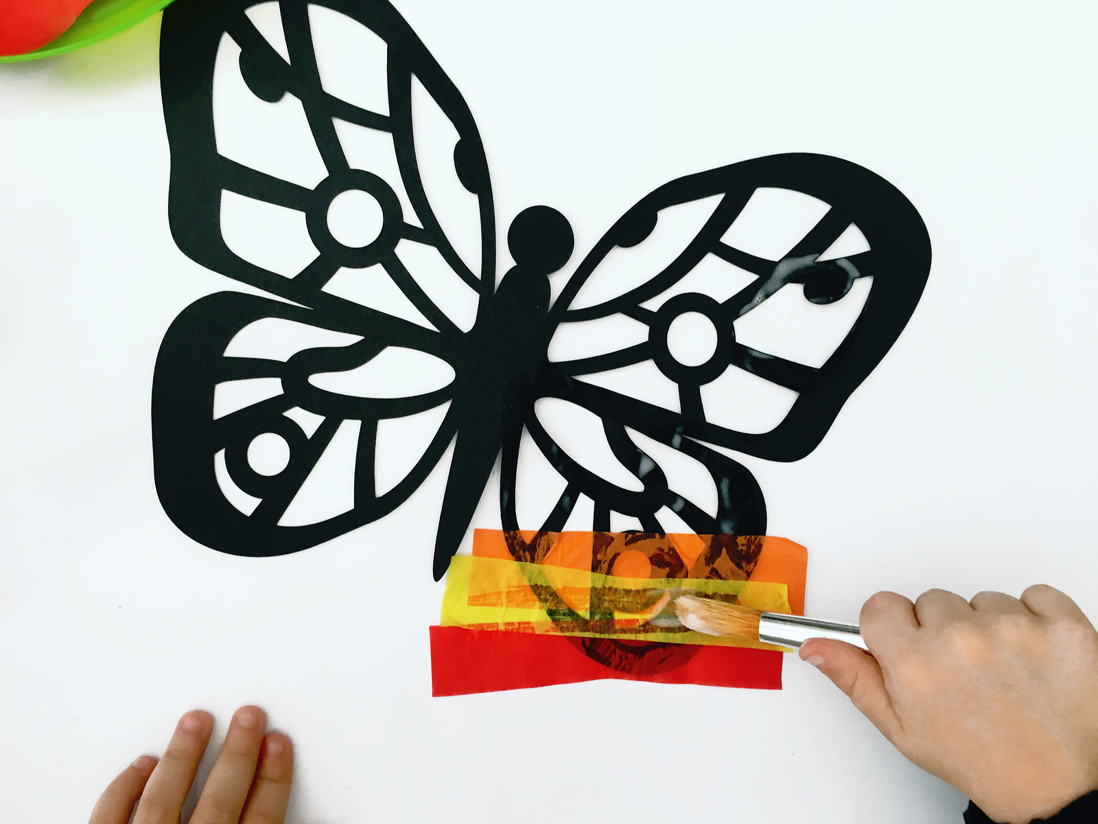toddler's hand applying glue to paper butterfly cut out