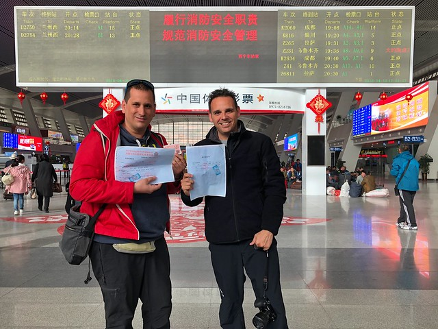 Sele e Isaac con los permisos del Tíbet en la estación de trenes de Xining
