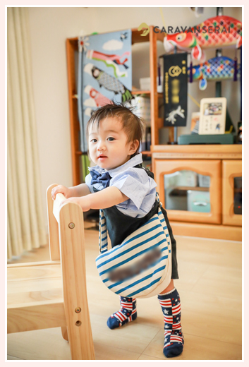 一升餅入りのバッグを担いで歩く1才の男の子