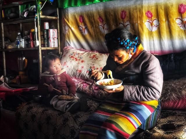 Mujer y niña comiendo noodles en el Campo Base Norte del Everest (Tíbet)