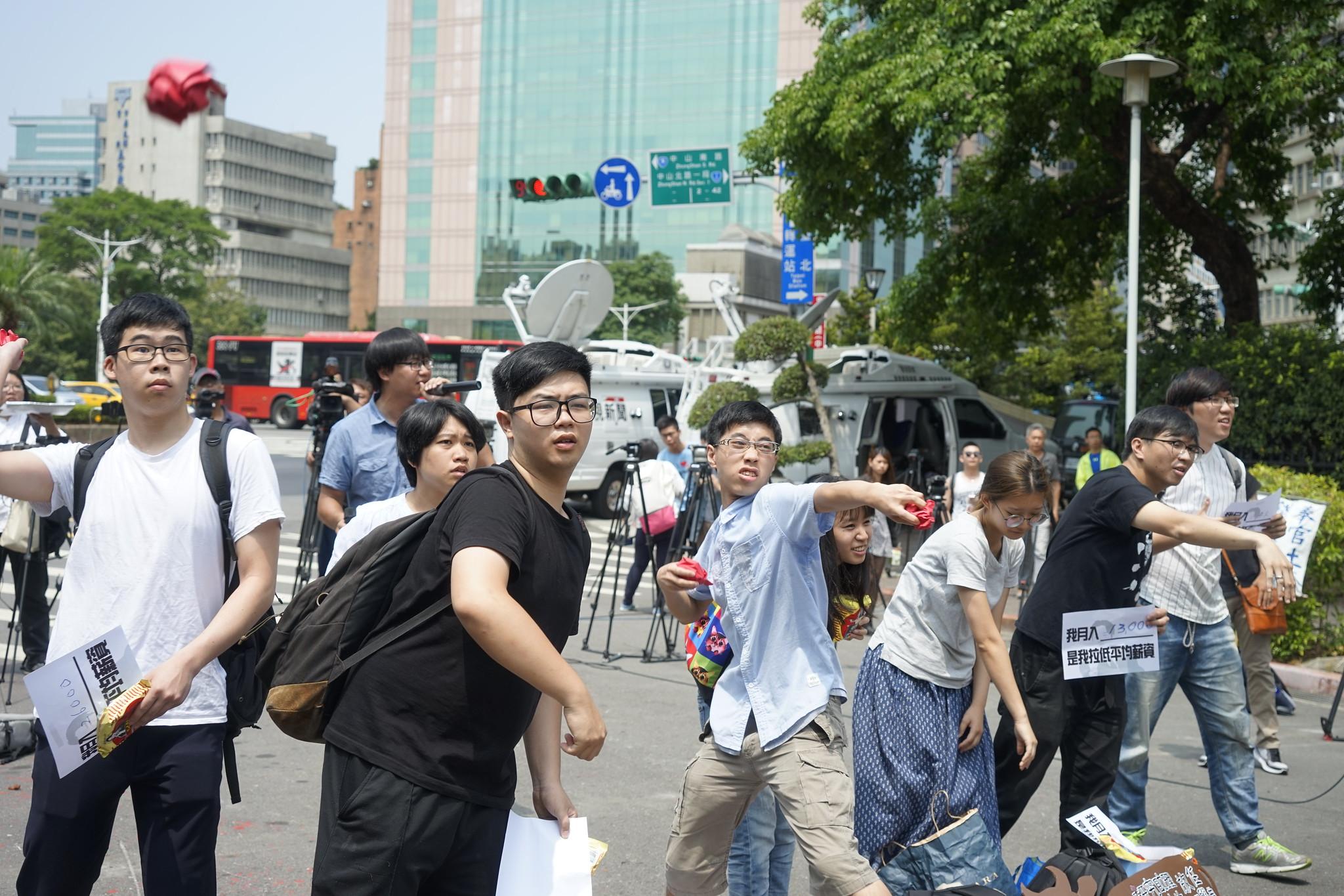 青年們將紅色的紙團捏成球,象徵政府端出的低薪「政策牛肉」,一一丟回行政院。(攝影:張宗坤)
