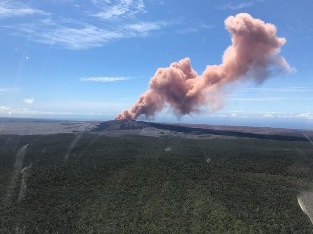 Image shows a view of a plume of pinkish ash spewing into blue skies, with green forests in the foreground.