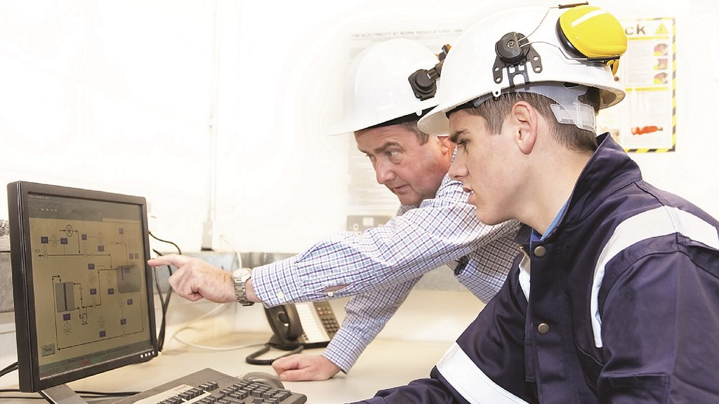 Two men looking at a computer screen wearing hard hats.