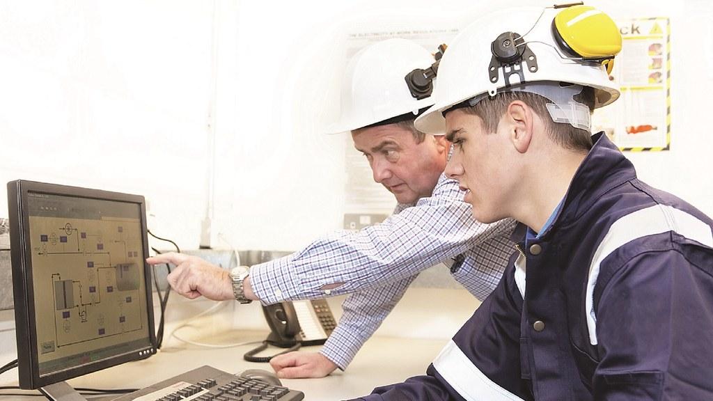 两个人戴着安全帽看着电脑屏幕.
