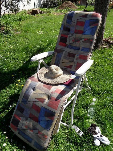 Liegestuhl mit Strohhut auf einer Wiese im Garten
