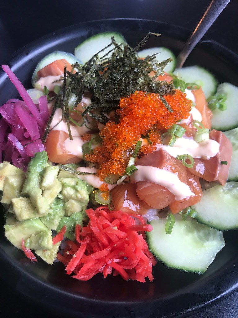 salmon poke bowl with fish roe, avocado, seaweed and cucumbers