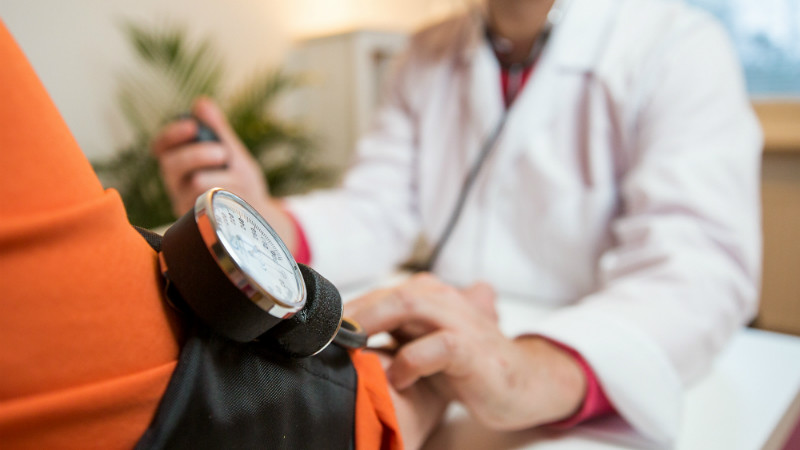 Doctor taking patients blood pressure representative of GP surgery.