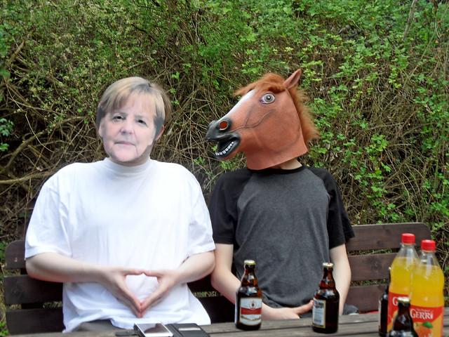 Zwei Jungs mit Masken von Angela Merkel und einem Pferd auf einer Bank