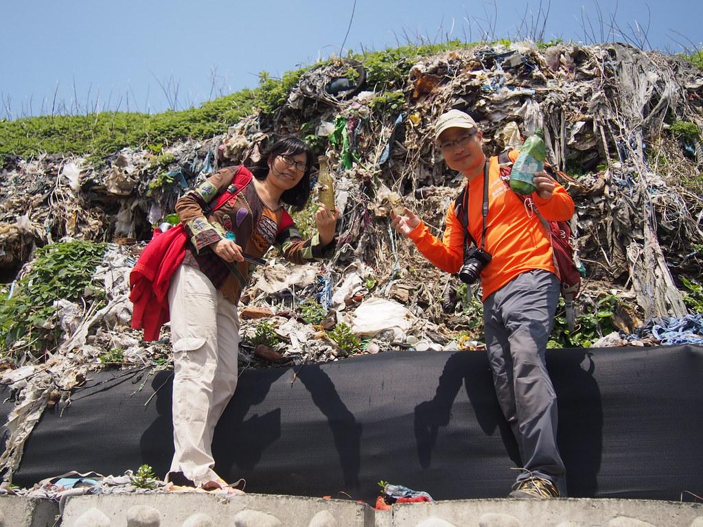 在潮境公園海邊可以看到垃圾裸露的地方,綠色人物觀察台灣三、四十年前產生的垃圾樣貌。攝影:陳宣竹。