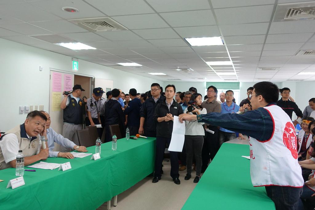 自救會成員鄭仲皓要求李文忠簽署承諾書。(攝影:張智琦)