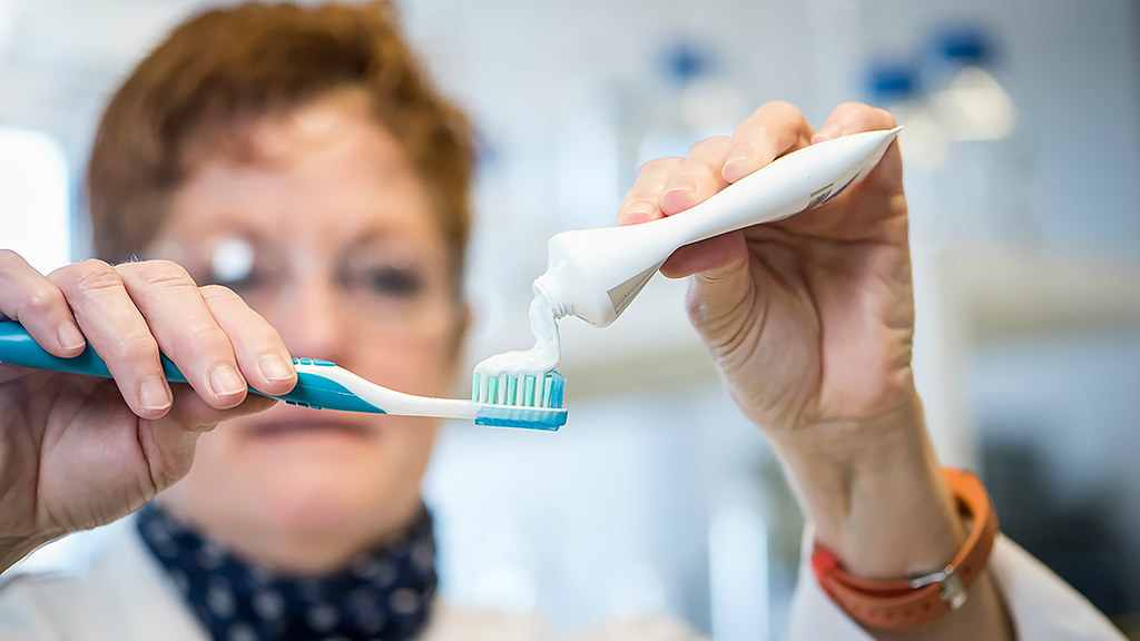 Professor Janet Scott putting toothpaste onto a toothbrush