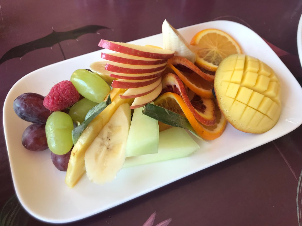 fruit plate of apples, grapes, berries, oranges, and mango