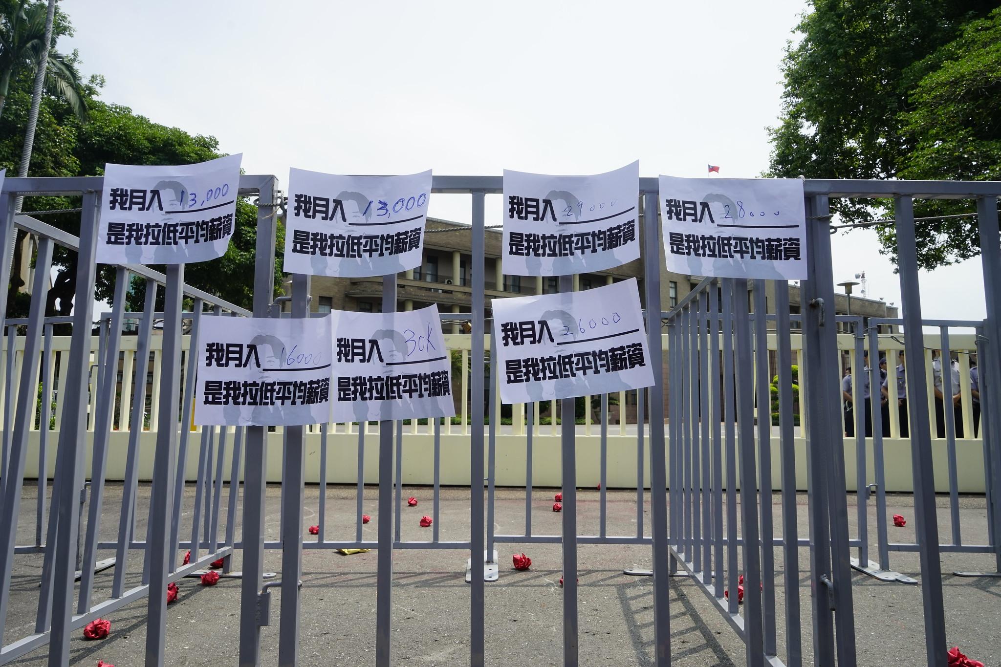 青年將薪資單貼在行政院圍籬上。(攝影:張宗坤)
