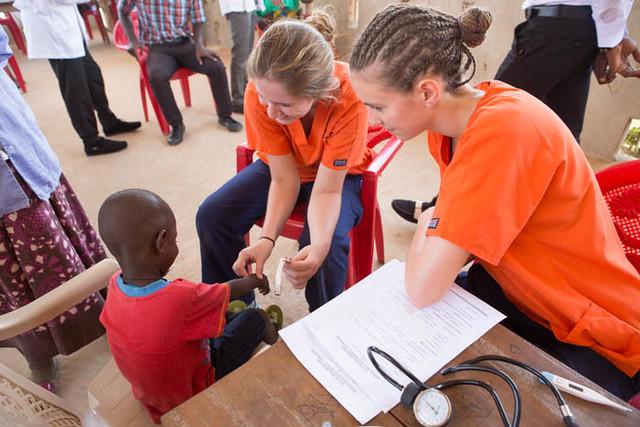 Two Auburn University nursing students provide care for a child in Ghana.