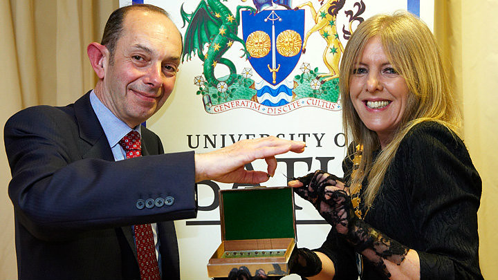 University treasurer Peter Wyman presents the peppercorn to Cllr Sarah Bevan, Chair of Bath & North East Somerset Council.