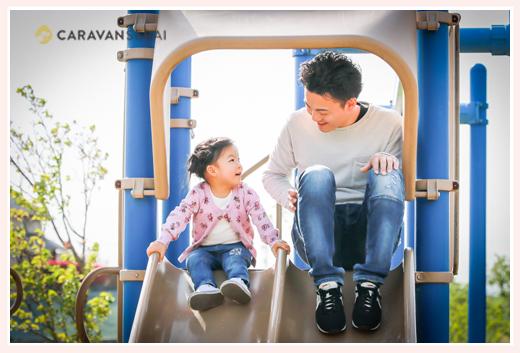 パパと楽しそうにすべり台を滑る女の子