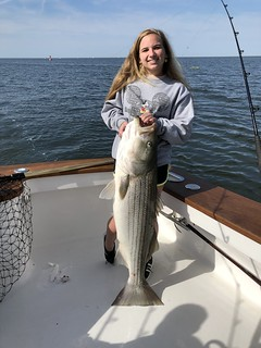 Photo of girl holding large striped bass she caught