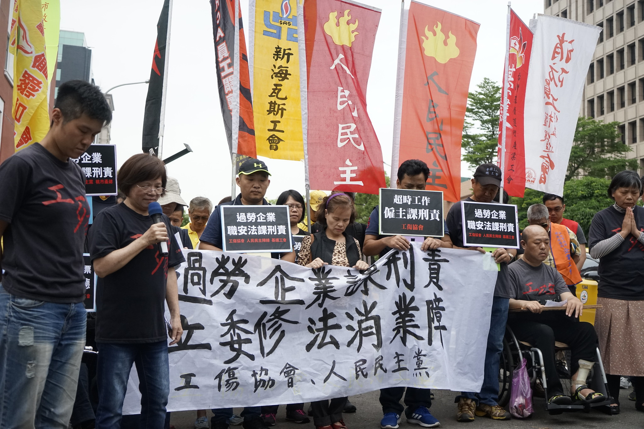 為了紀念近年來台灣過勞死的勞工,工傷協會在記者會開始後集體默哀。(攝影:張宗坤)