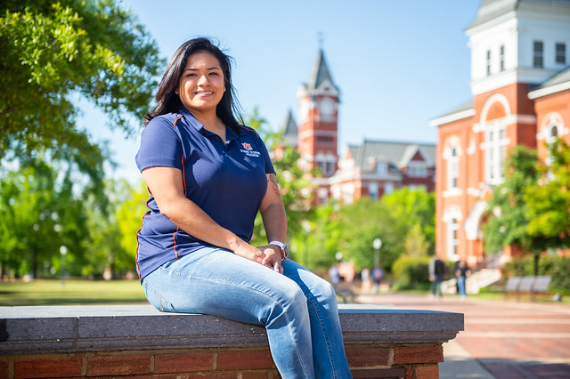 Melissa Villanueva is pictured sitting with Auburn's Samford Hall behind her