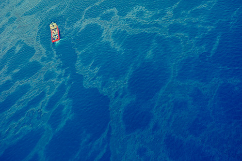 A tanker cuts a path through greasy ocean surface, as oil still pours out from the broken Horizon pipe line below. | by Kris Krug
