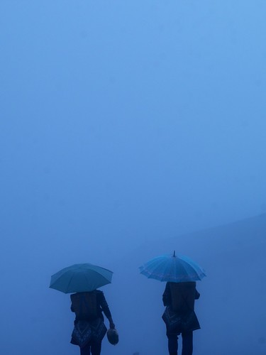 Two women with umbrellas in the fog and rain in Yuanyang, Yunnan, China | by Eric Lafforgue