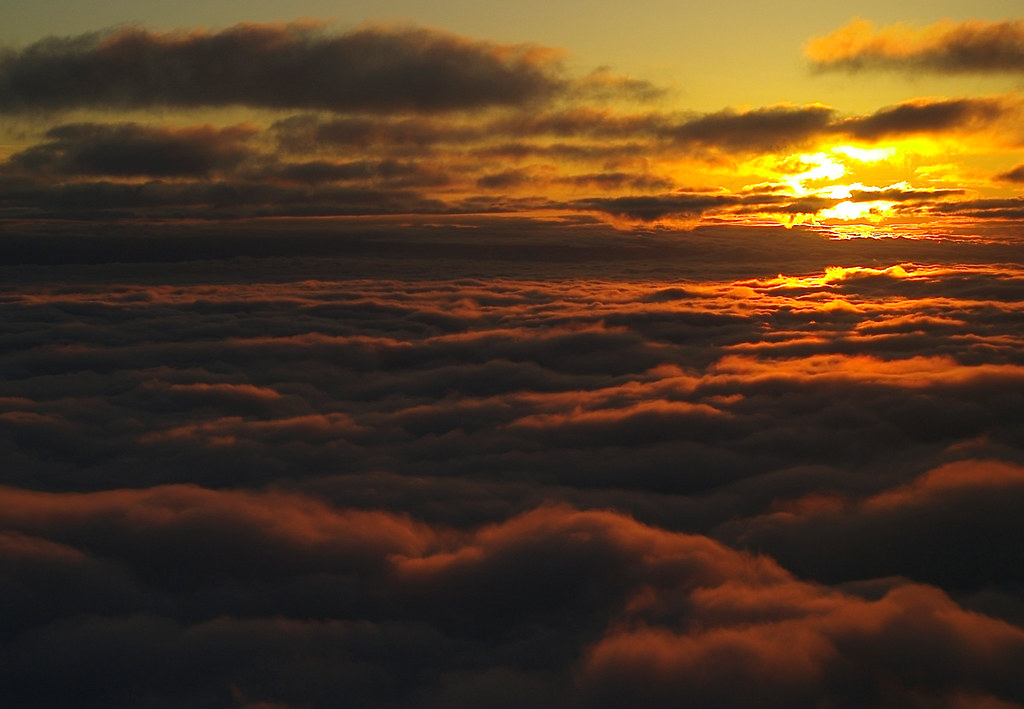 sun and layered nimbus clouds at dusk from the air flickr