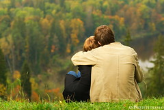 Sweet couple sitting on a hill and looking at the autumn landscape | by NejroN