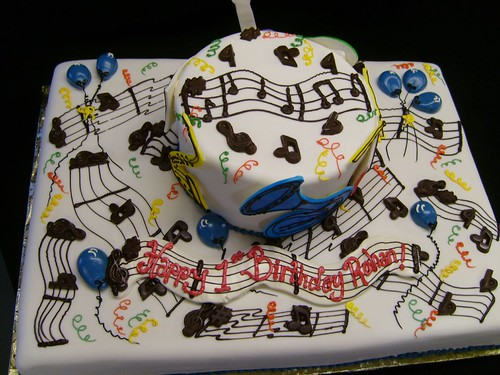 A Music Themed Cake With Chocolate Music Notes And Cut Out