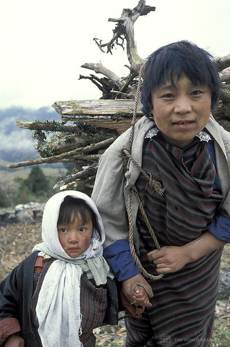 Woman and child. Woman carries wood.  Bhutan | by World Bank Photo Collection