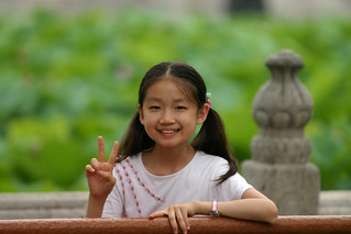 Little Girl Smiling and Giving Peace Sign | by Dan Zen