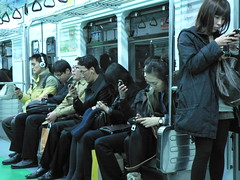 Everyone is staring at their phone, on the Seoul Metro, Seoul, Korea November 2010
