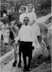 Two girls riding a donkey lead by boy | by Black History Album
