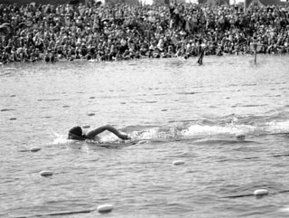 Swimmer Helene Madison swimming in a lake while a crowd watches in the background,Washington State | by UW Digital Collections