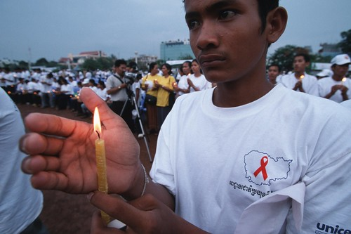 A campaigner holds a candle for HIV/AIDS victims at a rally | by World Bank Photo Collection