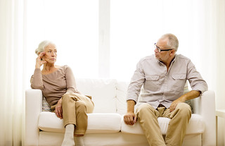senior couple sitting on sofa at home | by w5branding