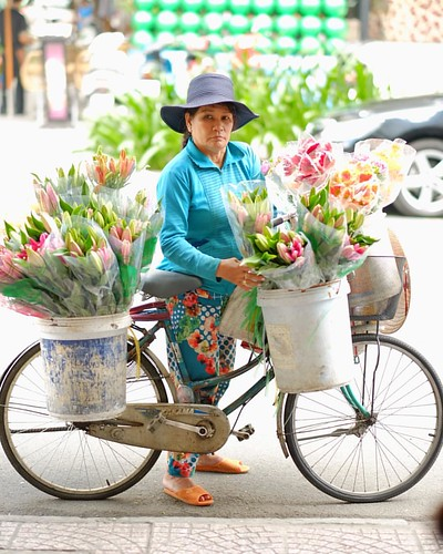 Vietnames flower vendor on bike at Ho Chi Minh. #meetthelocals #thecamhipster #vietnam | by Maan Pamintuan