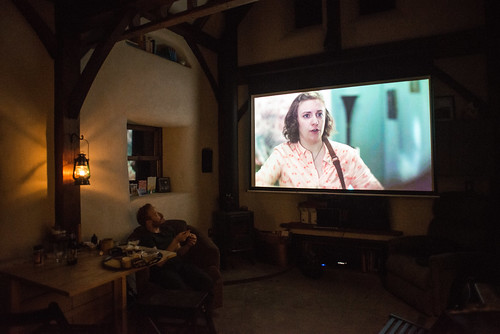 "Tiny Straw Bale Cottage Movie Theater: Tyler watching ""Girls"" on the Big Projector Screen 